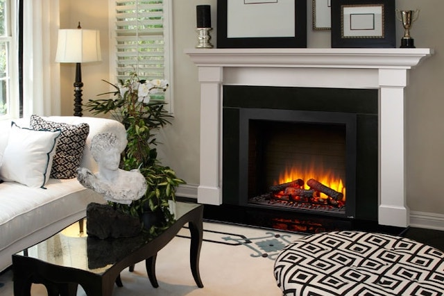 An electric fireplace built into a wall in a living room with taupe walls. The fireplace is bordered by a white mantel that has picture frames and other knick-knacks on top. In front of the fireplace is a white couch, coffee table, and black and white patterned stool.