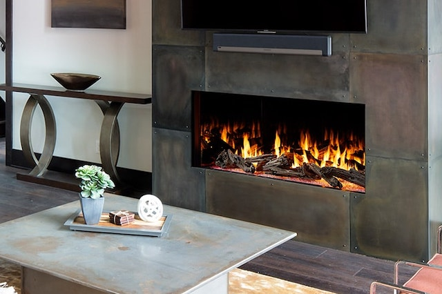 A photo of a living room with a modern gas fireplace with a flat screen tv mounted above it. In front of the fireplace is a rustic looking coffee table with trinkets and a succulent plant on top.