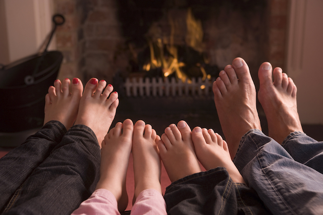 feet of a caucasion woman, little girl, little boy, and man respectively with a fireplace in the background. The viewer sees the family laying with their feet towards the fire