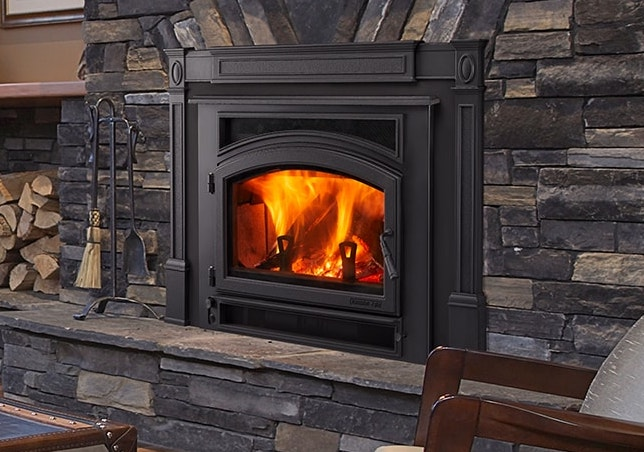 A photo of a  Quadra-Fire Expedition II Wood Insert with a fire in it inside of a living room.